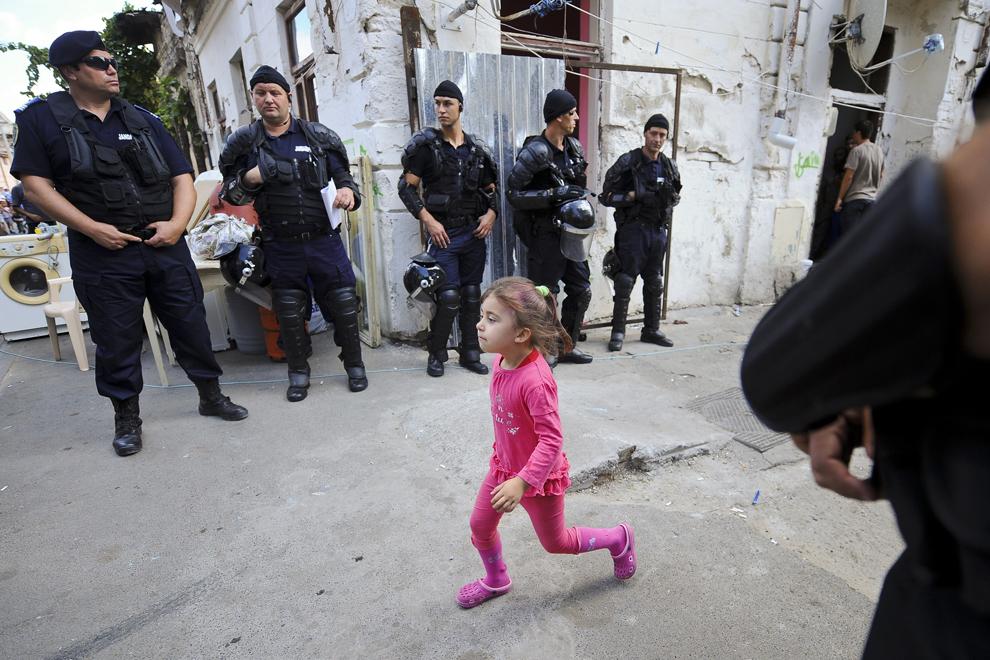 O fetiţă aleargă prin faţa jandarmilor postaţi la intrarea în ansamblul de locuinţe din strada Vulturilor, nr. 50, în Bucureşti, luni, 15 septembrie 2014. Aproximativ 100 de persoane, în curs de evacuare, reprezentând 25 de familii, care locuiau în mai multe case dintr-un gang, aflate în proprietate privată, au refuzat să meargă în adăposturile primăriei, unde femeile şi copiii ar sta separat de bărbaţi.
