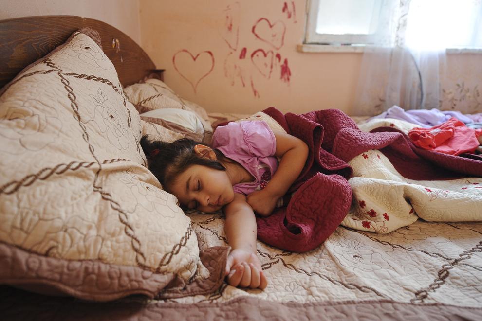 Eunice, un an şi trei luni, doarme într-o cameră ocupată ilegal de parinţii ei, în ansamblul de locuinţe de pe strada Vulturilor, nr. 50, în Bucureşti, luni, 15 septembrie 2014. Aproximativ 100 de persoane, în curs de evacuare, reprezentând 25 de familii, care locuiau în mai multe case dintr-un gang, aflate în proprietate privată, au refuzat să meargă în adăposturile primăriei, unde femeile şi copiii ar sta separat de bărbaţi.
