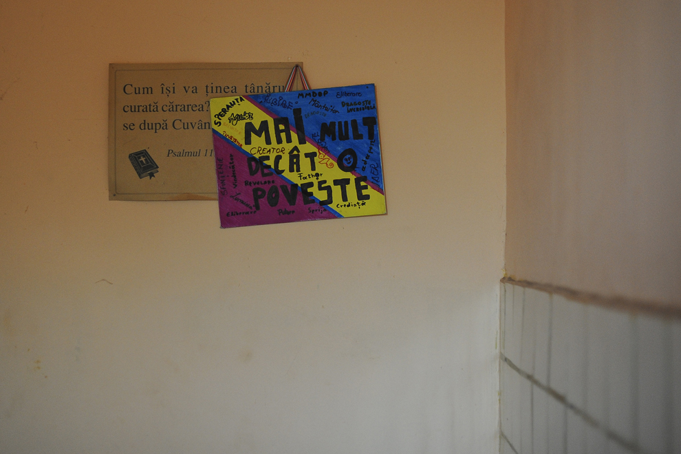 """O pancartă, în culorile tricolorului, pe care este scris textul """"Mai mult decât o poveste"""", este agăţată alături de o inscripţie religioasă, într-un imobil pe strada Vulturilor, numărul 50, în Bucureşti, luni, 15 septembrie 2014. Aproximativ 100 de persoane, în curs de evacuare, reprezentând 25 de familii, care locuiau în mai multe case dintr-un gang, aflate în proprietate privată, au refuzat să meargă în adăposturile primăriei, unde femeile şi copiii ar sta separat de bărbaţi."""