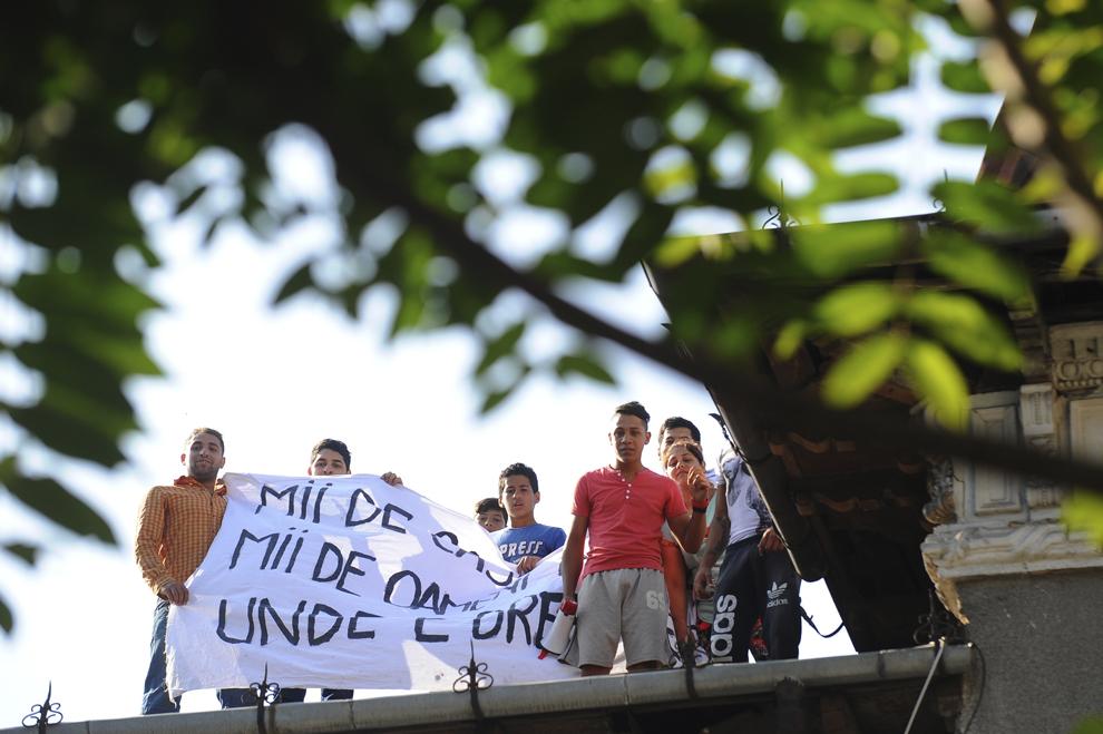 """O parte dintre persoanele evacuate din locuinţele de pe strada Vulturilor protestează faţă de aceasta măsură, arătând o pânză pe care scrie """"Mii de case goale, mii de oameni în strada. Unde e dreptatea?"""", în Bucureşti, luni, 15 septembrie 2014. Aproximativ 100 de persoane, în curs de evacuare, reprezentând 25 de familii, care locuiau în mai multe case dintr-un gang, aflate în proprietate privată, au refuzat să meargă în adăposturile primăriei, unde femeile şi copiii ar sta separat de bărbaţi."""