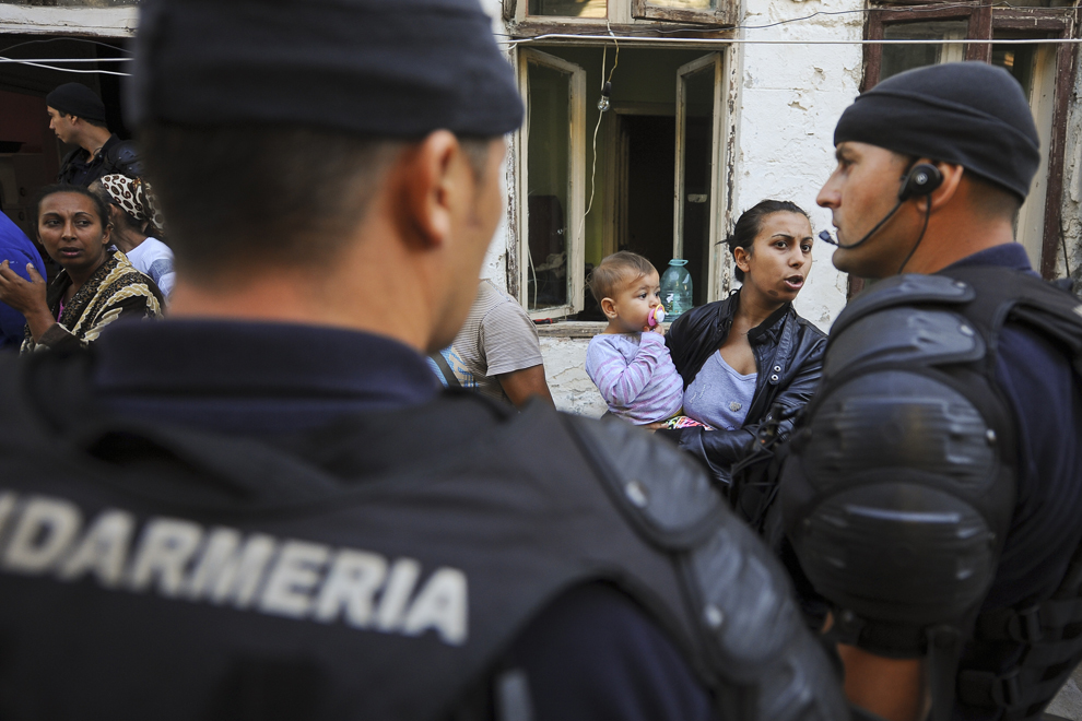 O femeie discută cu jandarmii care au descins în curtea ansamblului de imobile din strada Vulturilor, nr. 50, în Bucureşti, luni, 15 septembrie 2014. Aproximativ 100 de persoane, în curs de evacuare, reprezentând 25 de familii, care locuiau în mai multe case dintr-un gang, aflate în proprietate privată, au refuzat să meargă în adăposturile primăriei, unde femeile şi copiii ar sta separat de bărbaţi.