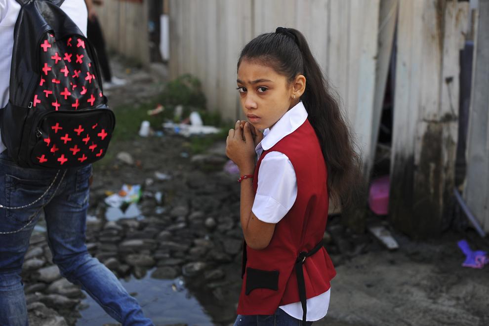 Alexandra, opt ani, elevă în clasa a II-a, priveşte spre aparatul de fotografiat, în curtea ansamblului de locuinţe de pe strada Vulturilor, nr. 50, în Bucureşti, luni, 15 septembrie 2014. Aproximativ 100 de persoane, în curs de evacuare, reprezentând 25 de familii, care locuiau în mai multe case dintr-un gang, aflate în proprietate privată, au refuzat să meargă în adăposturile primăriei, unde femeile şi copiii ar sta separat de bărbaţi.