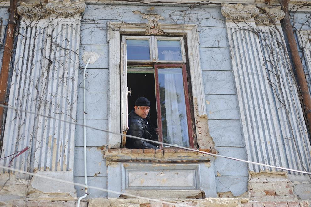 Un jandarm discută cu colegi ai săi de la geamul unei locuinţe din ansamblul de pe strada Vulturilor nr. 50, în Bucureşti, luni, 15 septembrie 2014. Aproximativ 100 de persoane, în curs de evacuare, reprezentând 25 de familii, care locuiau în mai multe case dintr-un gang, aflate în proprietate privată, au refuzat să meargă în adăposturile primăriei, unde femeile şi copiii ar sta separat de bărbaţi.