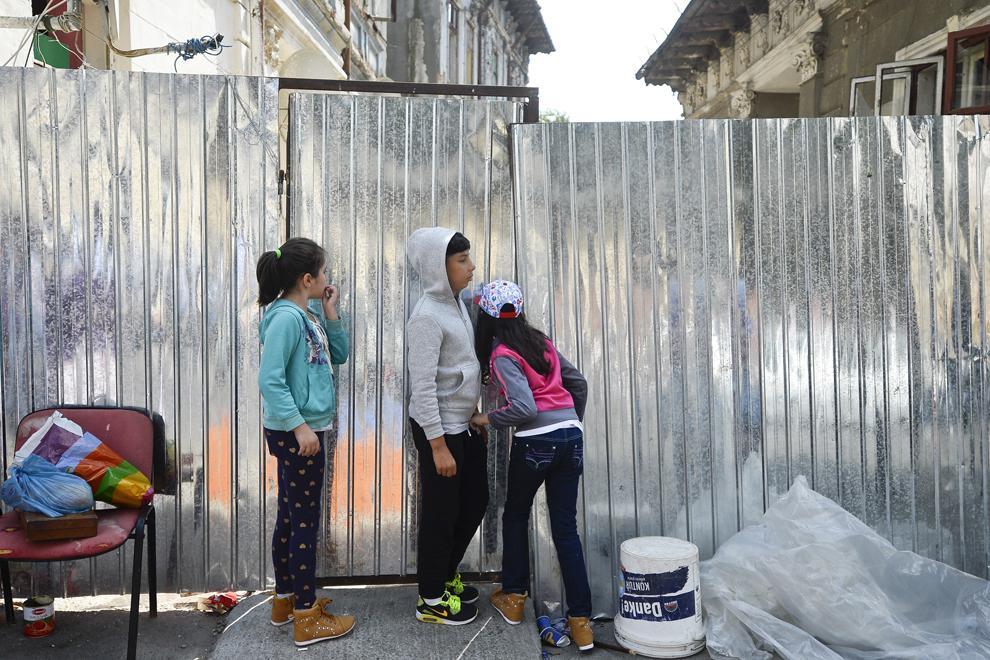 Trei copii se uită printr-un gard de tablă care împrejmuieşte ansamblul de locuinţe din care au fost evacuaţi, pe strada Vulturilor, nr. 50, în Bucureşti, marţi, 16 septembrie 2014.