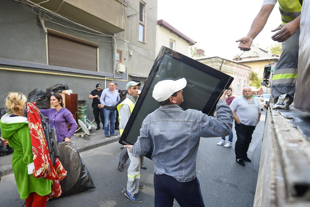 Persoane încarcă un televizor în bena unei autoutilitare, în timpul acţiunii forţelor de ordine pentru eliberarea trotuarelor de pe strada Vulturilor, ocupate de familiile evacuate din ansamblul de locuinţe de la numărul 50, în Bucureşti, marţi, 16 septembrie 2014.