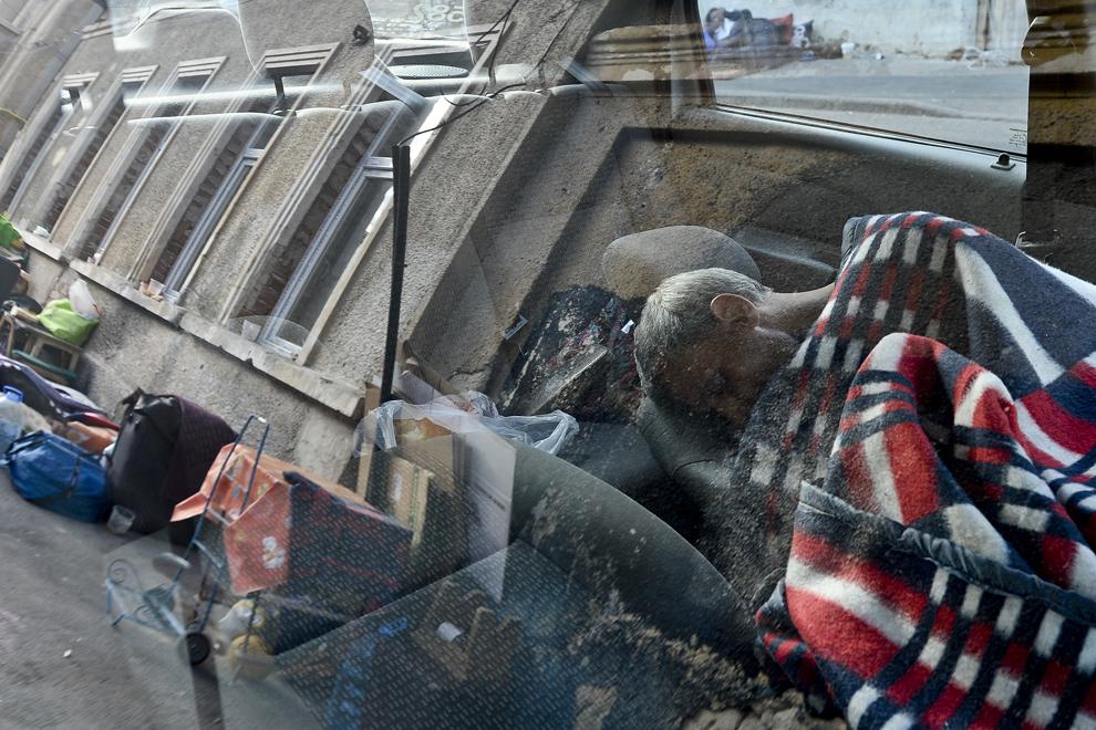 Un bărbat doarme în taximetrul cu care lucrează, vizavi de intrarea în ansamblul de case din care a fost evacuat, pe strada Vulturilor, nr. 50, în Bucureşti, miercuri, 17 septembrie 2014. Aproximativ 50 de persoane au dormit peste noapte în jurul intrării în fostele lor locuinţe, după ce au fost evacuaţi, luni, 15 septembrie.
