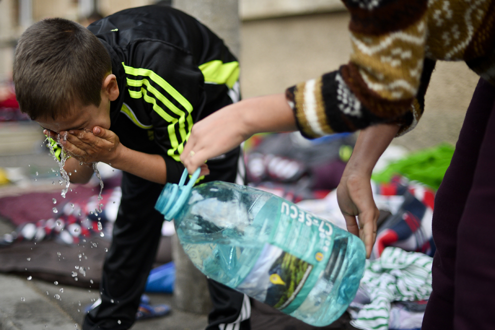 Un copil se spală pe faţă, după ce a dormit pe stradă, vizavi de intrarea în ansamblul de case din care a fost evacuat împreună cu familia lui, pe strada Vulturilor, nr. 50, în Bucureşti, miercuri, 17 septembrie 2014. Aproximativ 50 de persoane au dormit peste noapte în jurul intrării în fostele lor locuinţe, după ce au fost evacuaţi luni, 15 septembrie.