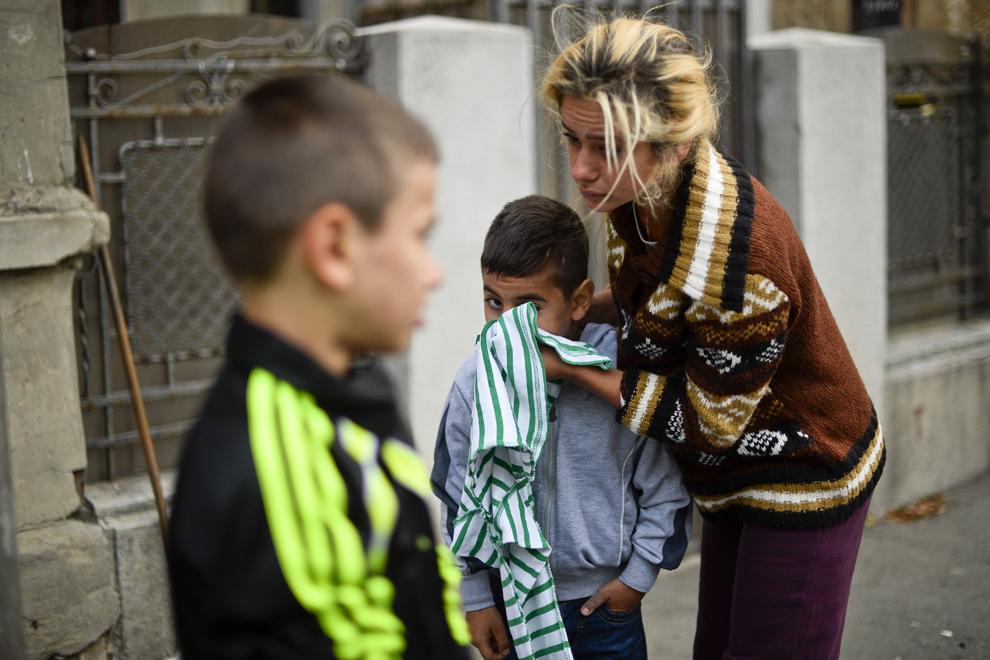 O mamă îşi spală copilul pe faţă, după ce au dormit pe stradă, vizavi de intrarea în ansamblul de case din care au fost evacuaţi, pe strada Vulturilor, nr. 50, în Bucureşti, miercuri, 17 septembrie 2014. Aproximativ 50 de persoane au dormit, peste noapte, în jurul intrării în fostele lor locuinţe, după ce au fost evacuaţi, luni, 15 septembrie.