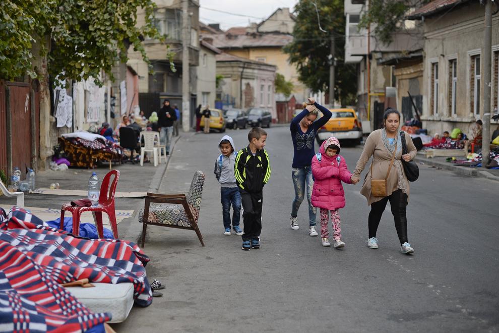 Trei copii sunt conduşi de mamele lor spre Şcoala Specială nr. 5, la două zile după ce au fost evacuaţi din ansamblul de case de pe strada Vulturilor, nr. 50, în Bucureşti, miercuri, 17 septembrie 2014. Aproximativ 50 de persoane au dormit peste noapte în jurul intrării în fostele lor locuinţe, după ce au fost evacuaţi, luni, 15 septembrie.
