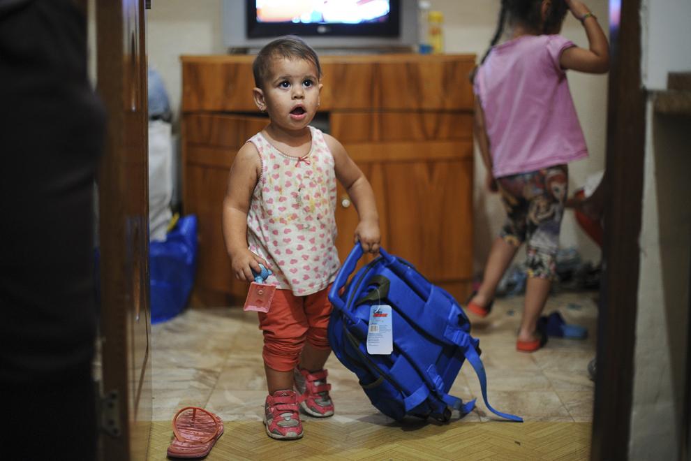 Erica, doi ani, se joacă cu ghiozdanul surorii ei mai mari, Bianca, în una dintre casele din gangul de pe strada Vulturilor, nr. 50, unde locuiesc, fără forme legale, aproximativ 100 de persoane care urmează a fi evacuate, în Bucureşti, duminică, 14 septembrie 2014.