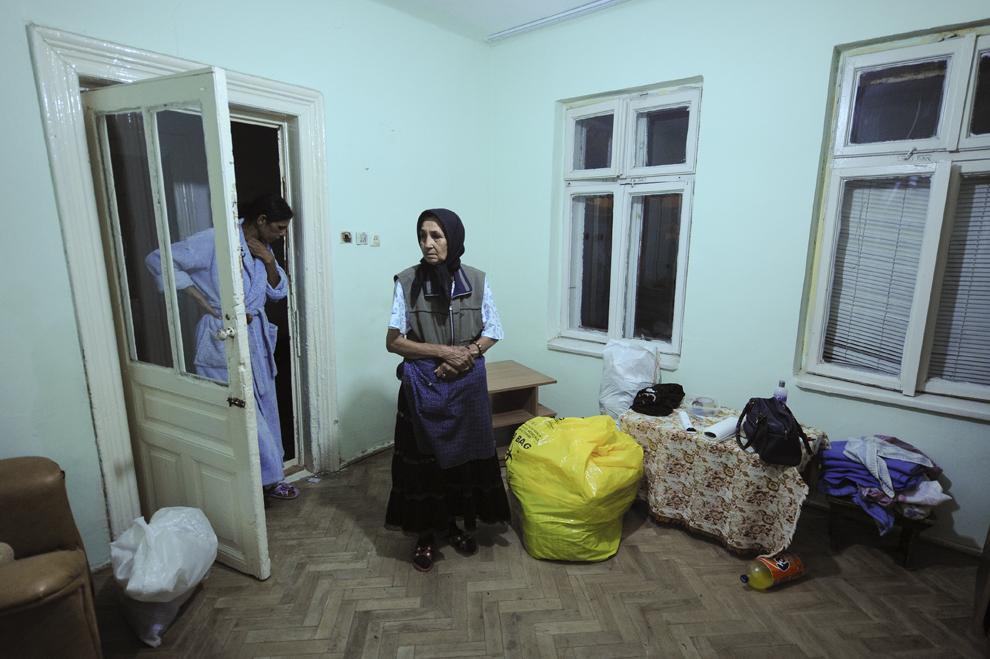 Tinca Ioana, pensionară, priveşte alături de fiica ei, spaţiul în care a locuit vreme de 30 de ani, în una din casele din gangul de pe strada Vulturilor nr. 50, unde locuiesc, fără forme legale, aproximativ 100 de persoane care urmează a fi evacuate, în Bucureşti, duminică, 14 septembrie 2014.