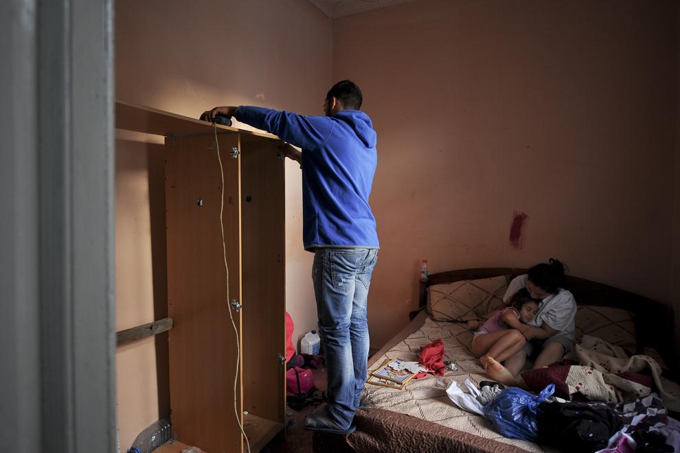Eunice, un an si trei luni, este îmbrăţişată de mama ei, în timp ce un bărbat demontează un şifonier, în interiorul imobilului ocupat ilegal pe strada Vulturilor, nr. 50, în Bucureşti, luni, 15 septembrie 2014. Aproximativ 100 de persoane, în curs de evacuare, reprezentând 25 de familii, care locuiau în mai multe case dintr-un gang, aflate în proprietate privată, au refuzat să meargă în adăposturile primăriei, unde femeile şi copiii ar sta separat de bărbaţi.