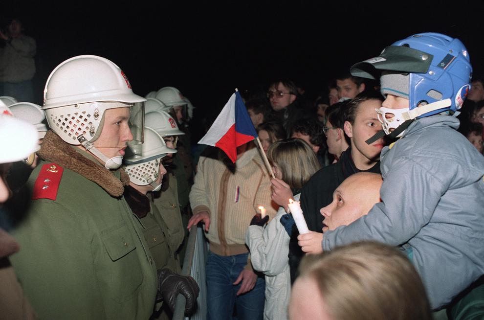 Un bărbat flutură un steag cehoslovac  în timp ce îşi ţine copilul pe umeri, în faţa unui cordon alcătuit din forţe de ordine, în centrul oraşului Praga, luni, 19 noiembrie 1989.