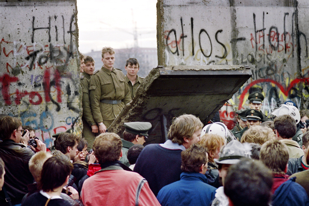 Locuitori din Berlinul de Vest privesc în timp ce grăniceri din Berlinul de Est dărâmă o porţiune a zidului Berlinului pentru a institui un nou punct de trecere a frontierei, sâmbătă, 11 noiembrie 1989.