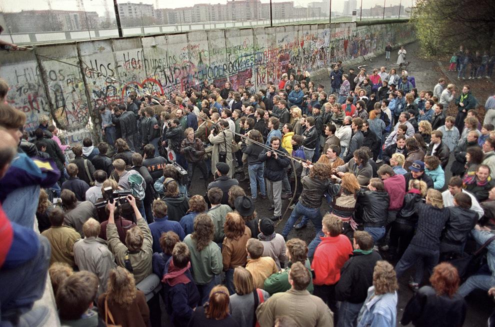 Locuitori din Berlinul de Vest încearcă să dărâme o porţiune a zidului Berlinului, sâmbătă, 11 noiembrie 1989.