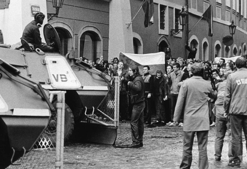 Forţe de ordine cehoslovace confruntă protestatari ce poartă steagul Cehoslovaciei, sâmbătă, 28 octombrie 1989, în centrul oraşului Praga.