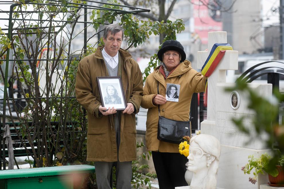 Angela Ignătescu şi Florian Ignătescu, pozează lângă mormântul rudei lor, Violeta Radu, decedată la vârstă de 33 de ani, în faţa magazinului Eva, în decembrie 1989. Violeta Radu era artist plastic.