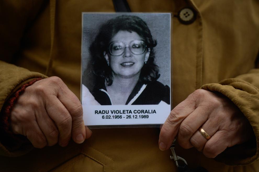Angela Ignătescu, în vârstă de 58 de ani, ţine în mâini fotografia verişoarei sale, Violeta Radu, decedată la vârstă de 33 de ani, în faţa magazinului Eva, în decembrie 1989. Violeta Radu era artist plastic.