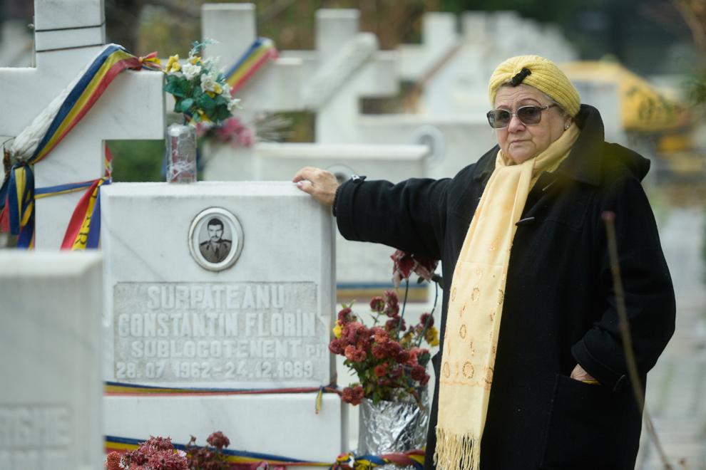 Ioana Surupăţeanu, în vârstă de 76 de ani, pozeaza lângă, mormântul fiului sau, Constantin Florin Surupăţeanu, decedat la vârsta de 27 de ani, în faţa MAPN, în  decembrie 1989. Constantin Florin Surupăţeanu era locotenent USLA.