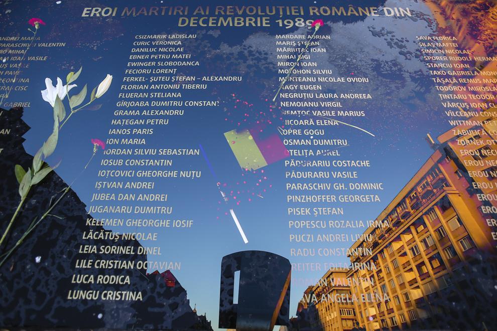 """Imagine cu expunere dublă compusă dintr-o placă pe care sunt gravate numele tuturor eroilor-martiri ai Revoluţiei române din Decembrie 1989 şi monumentul """"Crucificare"""" creat de sculptorul Paul Neagu (n. 1938, Bucureşti – d. 2004, Londra), în Piaţa Victoriei din Timişoara, sâmbătă, 20 decembrie 2014. Monumentul """"Crucificare"""" sugerează drumul crucii (via dolorosa) şi aminteşte neîncetat omului măsura dragostei lui Dumnezeu faţă de el. Esenţial în drumul crucii este faptul ca acela este locul de unde s-a început mântuirea oamenilor. În data de 20 decembrie 1989 în Piaţa Victoriei (fostă Operei) din municipiul Timişoara, acesta a fost proclamat primul oraş liber din România."""