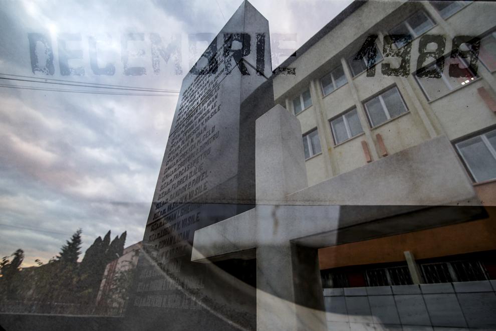 Imagine cu expunere dublă compusă din textul Decembrie 1989 şi Monumentul Eroilor Revoluţiei din faţa sediului Inspectoratului de Poliţie al Judeţului Sibiu, marţi, 16 decembrie 2014. Conform Ministerului Sănătăţii, în timpul Revoluţiei din decembrie 1989, în Sibiu au murit 99 de persoane şi peste 100 au fost rănite. Procurorii militari ce au anchetat cazul revoluţiei au estimat că numărul lor ar putea fi sensibil mai mare decât cifrele cunoscute oficial.