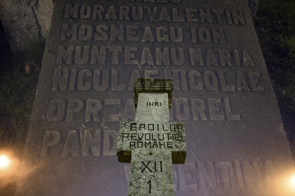 """Imagine cu expunere dublă compusă din numele martirilor ce au decedat în timpul Revolutiei din 1989 gravate pe o lespede de piatră, şi o cruce cu mesajul """"Eroilor Revoluţiei Române"""", realizată în Piaţa Universitaţii din Bucureşti, marţi, 16 decembrie 2014. Potrivit Secretariatului de Stat pentru Problemele Revoluţionarilor - 1142 de persoane au decedat şi 3138 au fost răniţi, cifrele fac referire doar la victimele care au fost declarate, înregistrate şi verificate conform legii. Procurorii militari ce au anchetat cazul revoluţiei au estimat că numărul lor ar putea fi sensibil mai mare decât cifrele cunoscute oficial."""