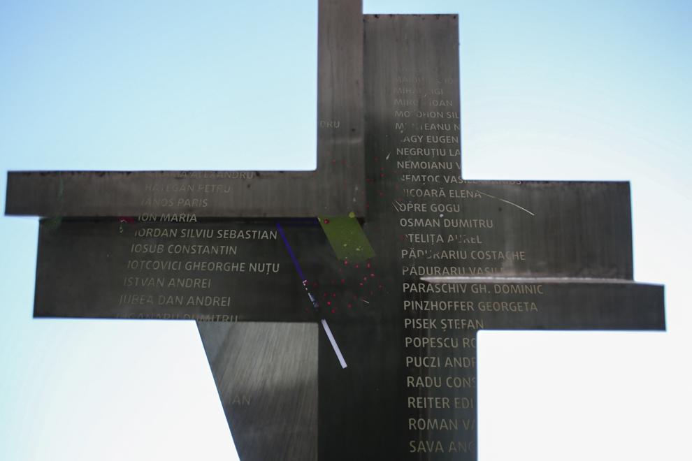 """Imagine cu expunere dublă compusă dintr-o placă pe care sunt gravate numele tuturor eroilor-martiri ai Revoluţiei române din Decembrie 1989 şi monumentul """"Crucificare"""" creat de sculptorul Paul Neagu (n. 1938, Bucuresti – d. 2004, Londra), în Piaţa Victoriei din Timişoara, sâmbătă, 20 decembrie 2014. Monumentul """"Crucificare"""" sugerează drumul crucii (via dolorosa) şi aminteşte neîncetat omului măsura dragostei lui Dumnezeu faţă de el. Esenţial în drumul crucii este faptul ca acela este locul de unde s-a început mântuirea oamenilor. În data de 20 decembrie 1989 în Piaţa Victoriei (fostă Operei) din municipiul Timişoara, Timişoara a fost proclamat primul oraş liber din România."""