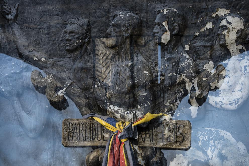 """Imagine cu expunere dublă compusă dintr-un basorelief, realizat de Ioan Iordănescu, ce decorează pereţii Crematoriului Uman Cenuşa şi o troiţă cu tricolor ridicată în memoria celor 43 de eroi-martiri decedaţi în decembrie 1989 în Timişoara şi incineraţi în Bucureşti în cadrul operaţiunii """"Trandafirul"""", realizată în Bucureşti, sâmbătă, 20 decembrie 2014. Operaţiunea Trandafirul s-a desfăşurat în zilele de 18 şi 20 decembrie 1989, în cadrul acţiunilor de reprimarea a Revoluţiei din decembrie 1989. 43 de cadavre ale celor împuşcaţi mortal la demonstraţiile din Timişoara în zilele de 16 şi 18 decembrie, dar şi ale unor răniţi executaţi în Spitalul Judeţean Timiş (SJT), au fost furate de la morga acestui spital şi transportate la Bucureşti, unde au fost incinerate în Crematoriul Uman Cenuşa. Cenuşa rezultată a fost aruncată într-un canal din Popeşti-Leordeni."""