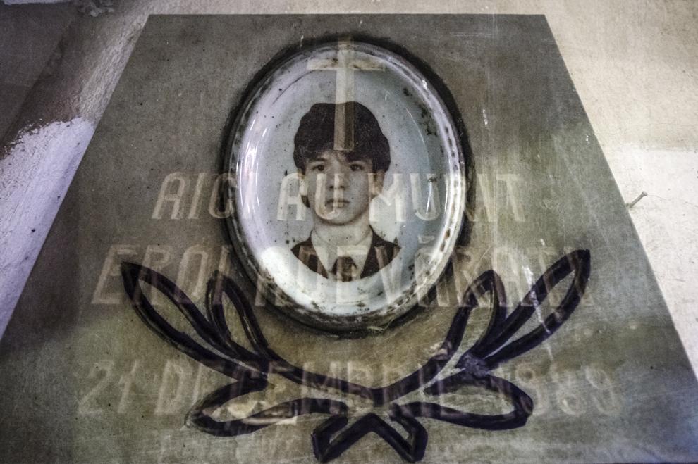 """Imagine cu expunere dublă compusă dintr-o plăcuţă cu mesajul """"Aici au murit Eroii Adevaraţi - 21 decembrie 1989"""" şi portretul lui Mihai Gîtlan, primul bucureştean ucis în timpul Revoluţiei din decembrie 1989, realizată în faţa Sălii Dalles din Bucureşti, marţi, 16 decembrie 2014. Potrivit martorilor, Mihai Gîtlan a fost rănit de un camion militar ce a intrat în plin într-un grup de tineri adunaţi lângă Sala Dalles, împuşcat cu mitralierele automate, de catre militari, apoi luat de păr, târât şi împuşcat în cap de către un civil. Mihai Gîtlan avea 19 ani."""