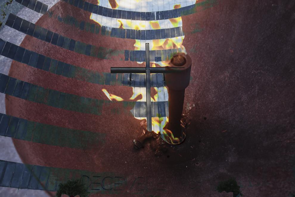 """Imagine cu expunere dublă compusă din flacăra eternă şi monumentul vertical, ambele proiectate de arh. Ionel Pop, ce fac parte din Complexul Memorial """"Memorialul Revoluţiei - Decembrie 1989"""" din Cimitirul Eroilor din Timişoara, sâmbătă, 20 decembrie 2014. Potrivit Secretariatului de Stat pentru Problemele Revoluţionarilor - 1142 de persoane au decedat şi 3138 au fost răniţi în toată ţara, cifrele fac referire doar la victimele care au fost declarate, înregistrate şi verificate conform legii. Conform Ministerului Sănătăţii, în timpul Revoluţiei din decembrie 1989, în Timişoara au murit 93 de persoane şi 373 au fost rănite. Procurorii militari ce au anchetat cazul revoluţiei au estimat că numărul lor ar putea fi sensibil mai mare decât cifrele cunoscute oficial."""