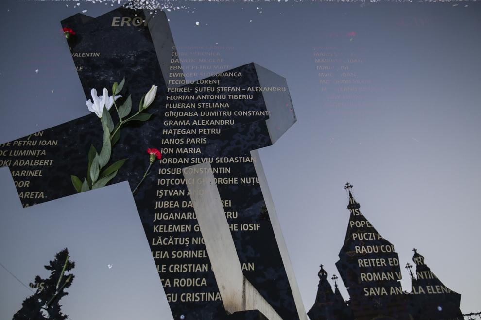 """Imagine cu expunere dublă compusă dintr-o placă pe care sunt gravate numele tuturor eroilor-martiri ai Revoluţiei Române din Decembrie 1989 şi monumentul """"Crucificare"""" creat de sculptorul Paul Neagu (n. 1938, Bucureşti – d. 2004, Londra), în Piaţa Victoriei din Timişoara, sâmbătă, 20 decembrie 2014. Monumentul """"Crucificare"""" sugerează drumul crucii (via dolorosa) şi aminteşte neîncetat omului măsura dragostei lui Dumnezeu faţă de el. Esenţial în drumul crucii este faptul ca acela este locul de unde s-a început mântuirea oamenilor. În data de 20 decembrie 1989 în Piaţa Victoriei (fostă Piaţa Operei) din municipiul Timişoara, acesta a fost proclamat primul oraş liber din România."""