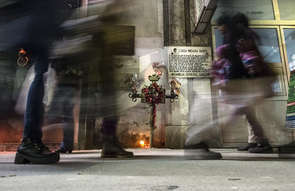 Persoane trec pe lângă troiţa de la Sala Dalles din Bucureşti, marţi, 16 decembrie 2014. În jurul orei 17, în data de 21 decembrie 1989, 13 tineri au murit (6 striviţi de un camion militar şi 7 împuşcaţi) în faţa Salii Dalles. Acestea au fost primele victime din Bucureşti ale Revoluţiei din decembrie '89. Potrivit Secretariatului de Stat pentru Problemele Revoluţionarilor - 1142 de persoane au decedat şi 3138 au fost răniţi, cifrele fac referire doar la victimele care au fost declarate, înregistrate şi verificate conform legii. Procurorii militari ce au anchetat cazul revoluţiei au estimat că numărul lor ar putea fi sensibil mai mare decât cifrele cunoscute oficial.