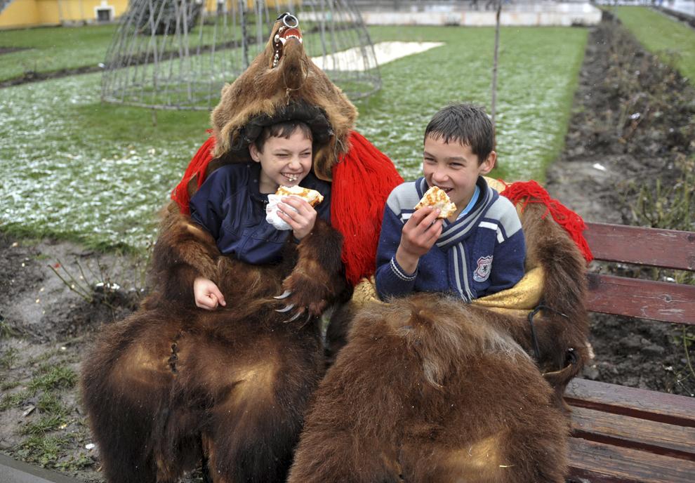 Doi copii costumaţi în urşi mănâncă pe o bancă din Bacău, în timpul Festivalului tradiţiilor şi obiceiurilor, în Bacău, sâmbătă, 27 decembrie 2014.