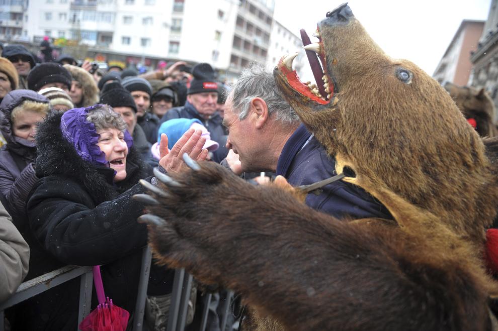 Un bărbat costumat în urs discută cu o femeie aflată în public, în timpul Festivalului tradiţiilor şi obiceiurilor, în Bacău, sâmbătă, 27 decembrie 2014.