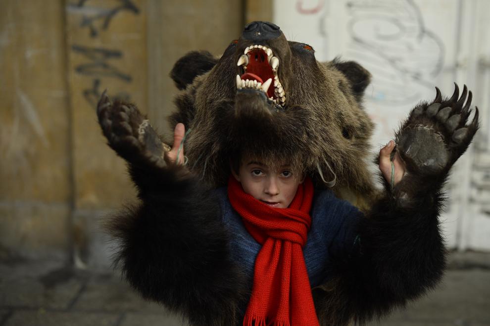 Florin Borş, 8 ani, costumat în urs, din comuna Dofteana, judeţul Bacău, dansează pe străzile din centrul Bucureştiului, marţi, 15 decembrie 2014.