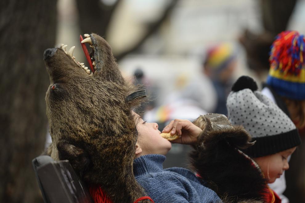 Un copil costumat în urs, din comuna Dofteana, judeţul Bacău, mănâncă pe o bancă dintr-un parc din centrul Bucureştiului, marţi, 23 decembrie 2014.