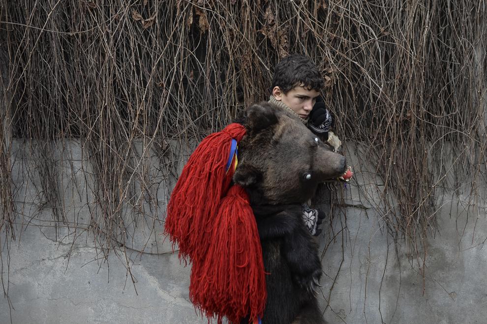 Un copil costumat în urs, din comuna Dofteana, judeţul Bacău, vorbeşte la telefon, în centrul Bucureştiului, marţi, 23 decembrie 2014.