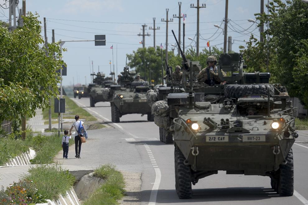 """O femeie ţine de mână un copil pe o stradă străbătută de o coloană formată din transportoare militare blindate """"Stryker"""" în timpul deplasării acestora prin judeţul Ialomiţa, miercuri, 13 mai 2015."""