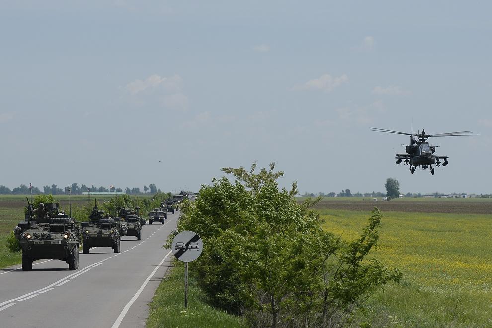 """Un elicopter militar de atac AH-64 Apache însoţeşte o coloană formată din transportoare militare blindate """"Stryker"""" în timpul deplasării acestora prin judeţul Prahova, miercuri, 13 mai 2015."""