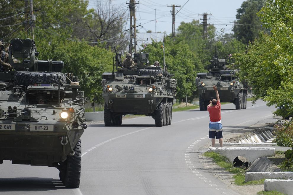 """Un bărbat filmează şi salută o coloană formată din transportoare militare blindate """"Stryker"""" în timpul deplasării acestora prin judeţul Prahova, miercuri, 13 mai 2015."""