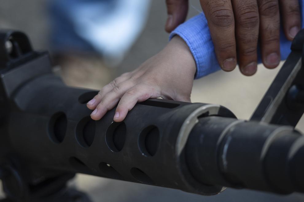 """Un copil atinge ţeava unei mitraliere de calibru .50 în timpul evenimentului """"Marşul Cavaleriei""""din parcarea unui mall din Ploieşti, miercuri, 13 mai 2015."""