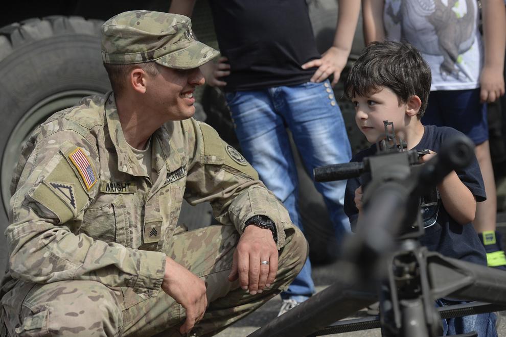 """Un copil priveşte către sergentul Wright care îi prezintă o mitralieră de calibrul .50 în timpul evenimentului """"Marşul Cavaleriei""""din parcarea unui mall din Ploieşti, miercuri, 13 mai 2015."""