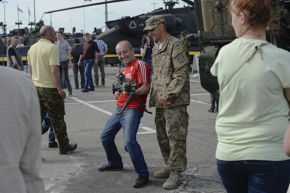 """Un bărbat ţine în mână o mitralieră în timpul evenimentului """"Marşul Cavaleriei""""din parcarea unui mall din Ploieşti, miercuri, 13 mai 2015."""