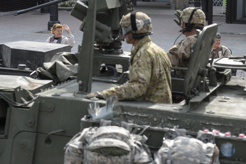 """Două femei salută trecerea prin oraşul Sinaia a unei coloane de vehicule militare """"Stryker"""", joi, 14 mai 2015."""