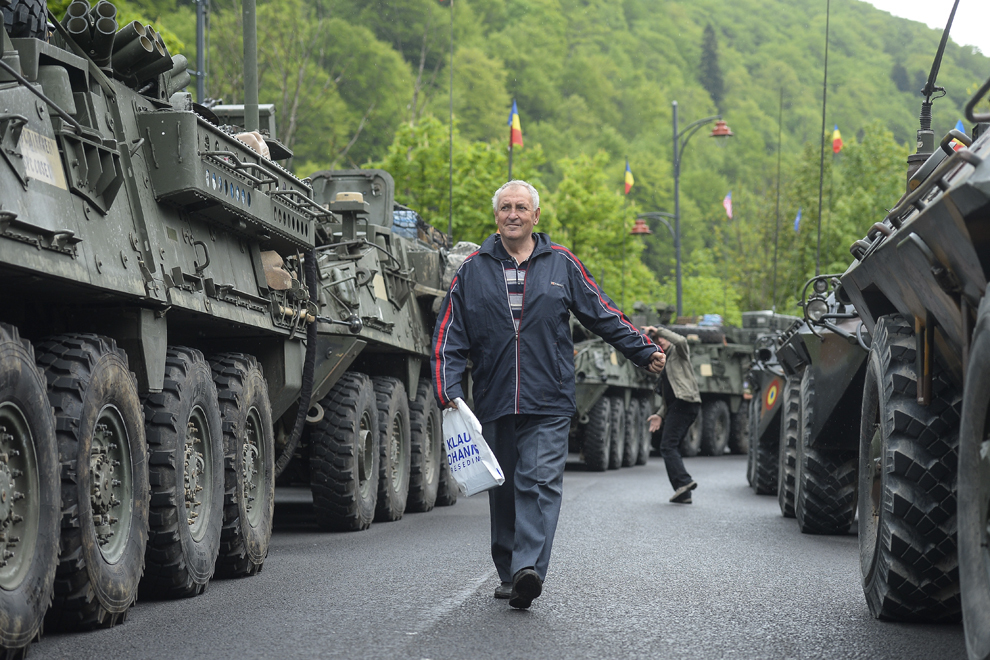 """Un bărbat trece printre vehicule militare americane şi române parcate pe Bulevardul Ferdinand din Sinaia, în timpul evenimentului """"Marşul Cavaleriei"""", joi, 14 mai 2015."""