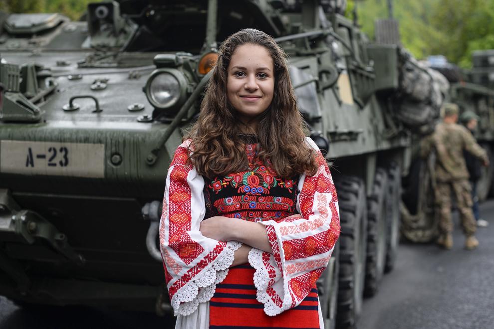 """Andra Ştefan, 14 ani, elevă, pozează îmbrăcată în port tradiţional în faţa unui transportor militar blindat """"Stryker"""" parcat pe Bulevardul Ferdinand din Sinaia, în timpul evenimentului """"Marşul Cavaleriei"""", joi, 14 mai 2015."""