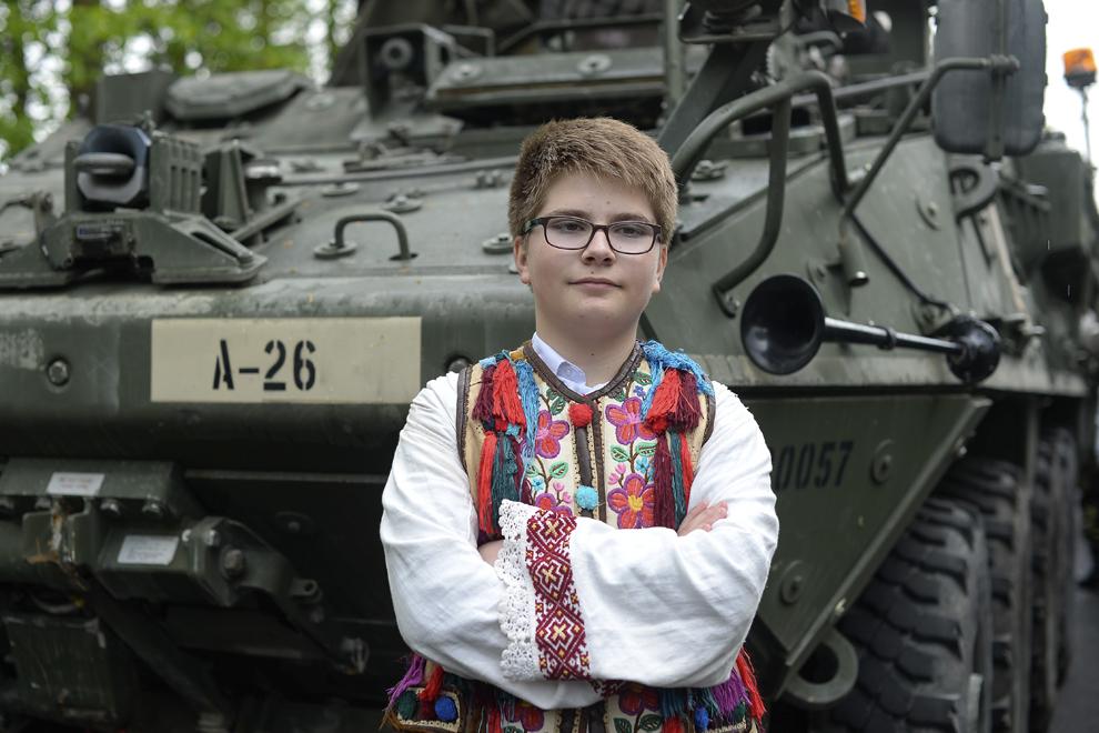 """Telegescu Ionuţ, 14 ani, elev, pozează îmbrăcat în port tradiţional în faţa unui transportor militar blindat """"Stryker"""" parcat pe Bulevardul Ferdinand din Sinaia, în timpul evenimentului """"Marşul Cavaleriei"""", joi, 14 mai 2015."""