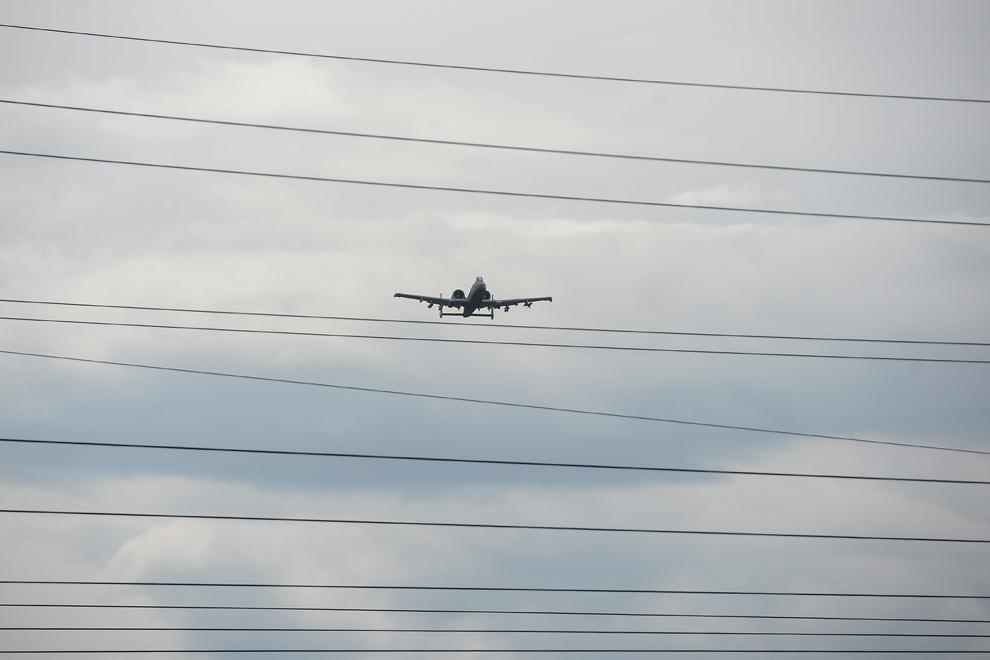 """Un avion de atac A-10 Warthog este vizibil printre fire de înaltă tensiune în apropierea oraşului Braşov, în timpul evenimentului """"Marşul Cavaleriei"""", joi, 14 mai 2015."""