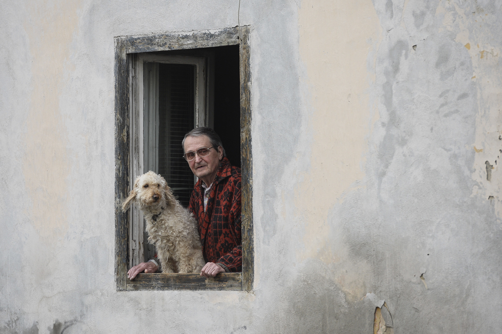 """Un bărbat priveşte de la geamul casei sale alături de câinele lui trecerea unei  coloane de transportoare militare blindate """"Stryker"""" care străbate oraşul Braşov în timpul evenimentului """"Marşul Cavaleriei"""", joi, 14 mai 2015."""