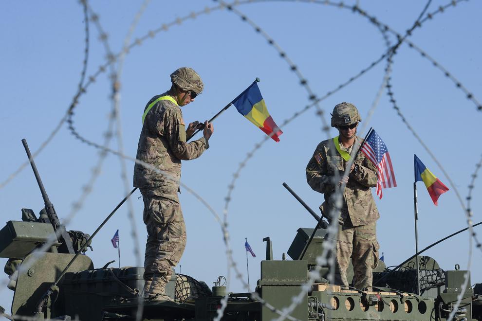 """Soldaţi americani prind steagurile României şi Statelor Unite ale Americii pe antenele unui transportor blindat """"Stryker"""", în baza militară Mihail Kogalniceanu, miercuri, 13 mai 2015."""
